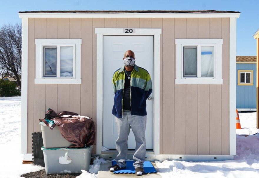"""Taron Williams and his wife moved into their beige #20 tiny home a couple weeks ago. """"I'm blessed,"""" he says. The couple is waiting on a spot in permanent housing to open up. They were evicted from a tent encampment near the McGuire Moving & Storage building in early January."""