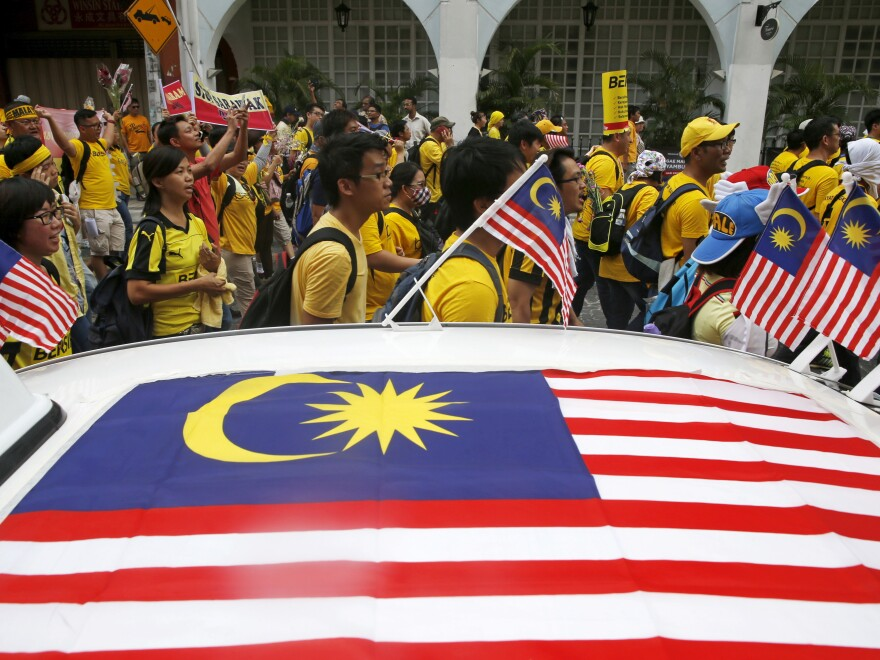 """Supporters of pro-democracy group """"Bersih"""" (Clean) pass a taxi decorated with Malaysian flags as they march toward Dataran Merdeka in Malaysia's capital city of Kuala Lumpur, on Saturday. The group is protesting alleged corruption at the top levels of government."""