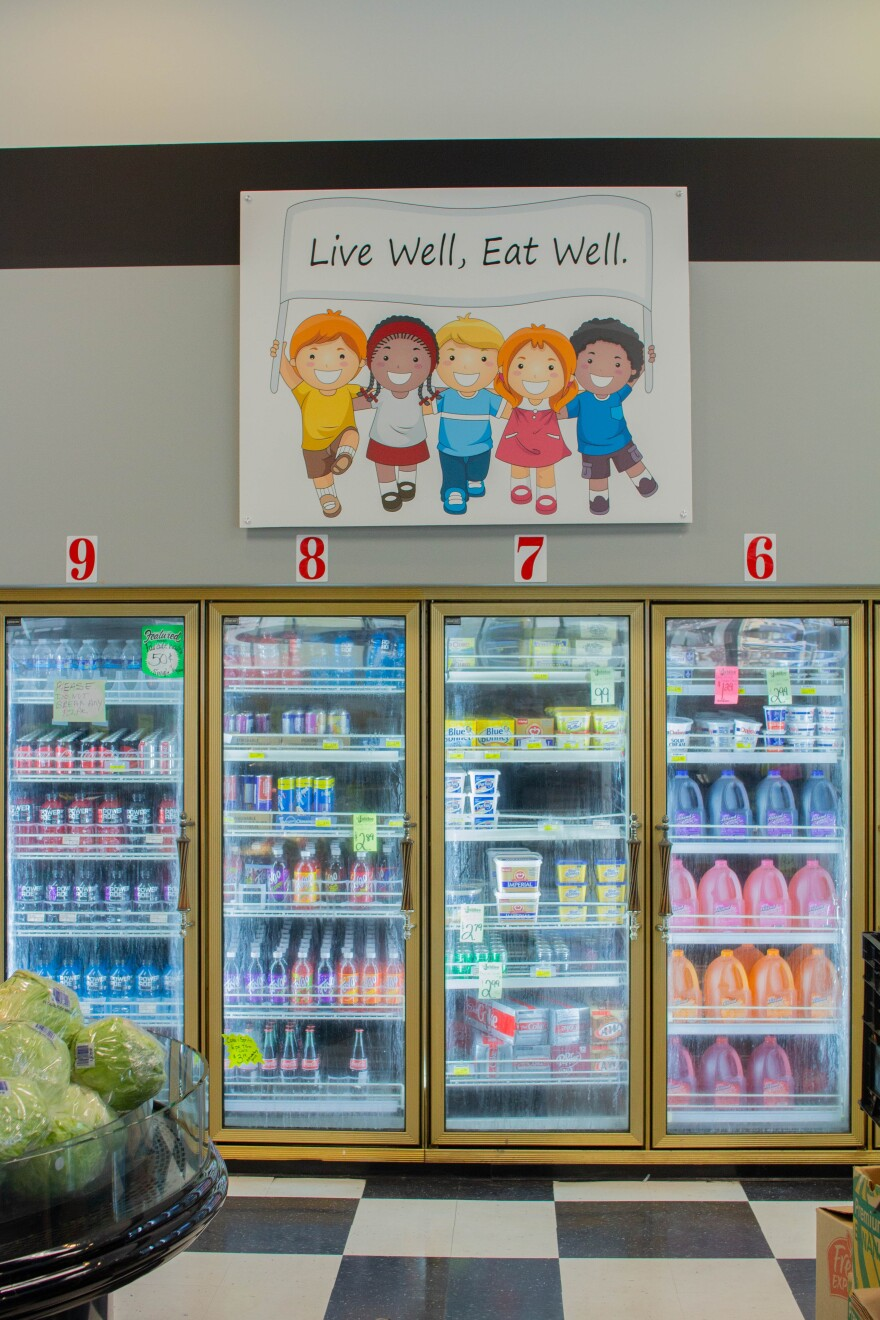 """A sign reads """"Live Well, Eat Well"""" above the refrigerated cases at a grocery store."""