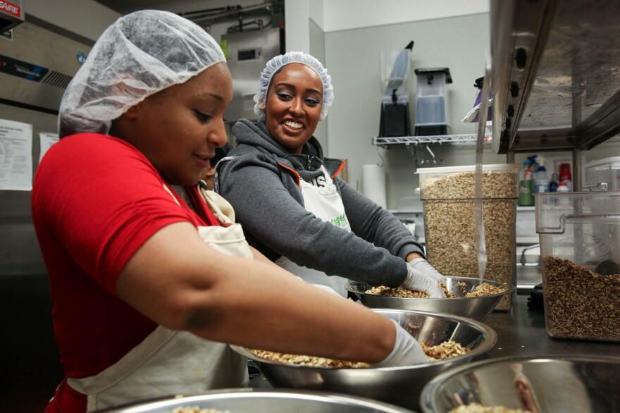 Nikki Yates, a program participant, and Hanna Teklu, a graduate of the program and now a program assistant, mix granola.