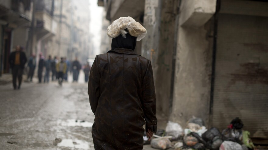 A Syrian woman carries a ration of bread on her head in the northern city of Aleppo. The Syrian opposition now runs local councils in many cities, particularly in the north. They often face major challenges in providing basics likes food, water and electricity.