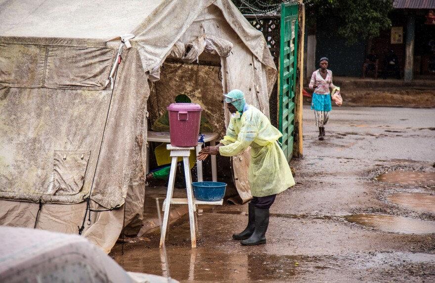 A health worker cleans his hands with chlorinated water before entering an Ebola screening tent Monday at a government hospital in Kenema, Sierra Leone. The World Health Organization cites 1,848 cases of the deadly disease across West Africa.