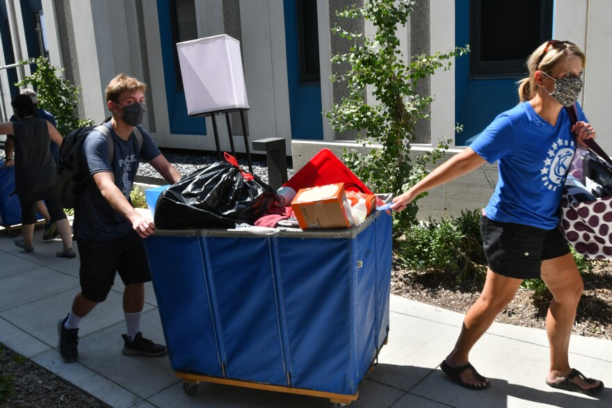 Freshman student and his mom hauling up a load of dorm furnishings and supplies to Barbara Marshall Residence Hall.