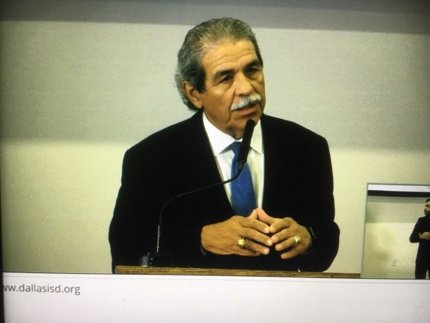photo of a man, Dallas superintendent Michael Hinojosa, standing at a lectern speaking into a microphone