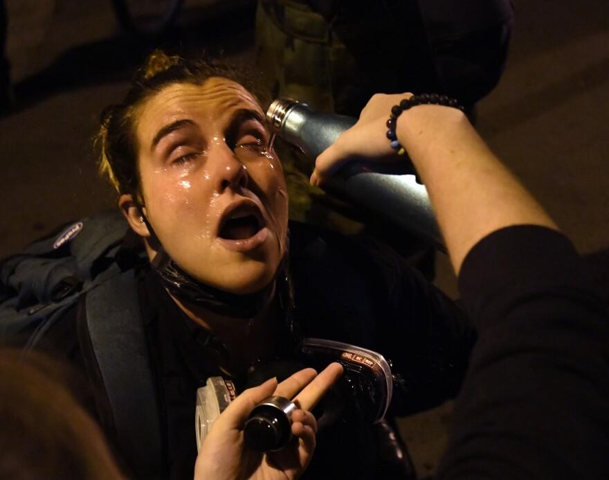 A protestor gets her eyes flushed after clashes broke out on Black Lives Matter Plaza.