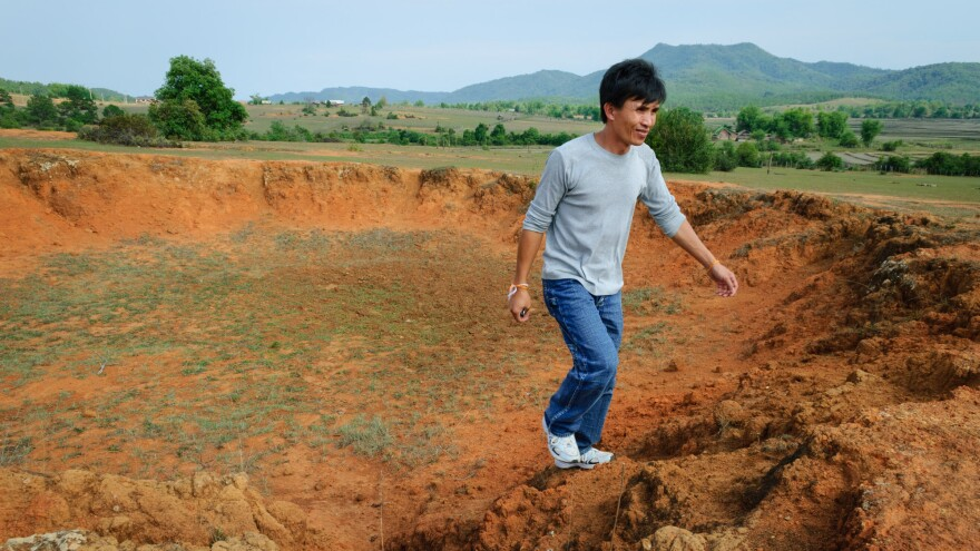 Manophet climbs out of a crater in rural Xieng Khouang, Laos — a remnant of the U.S. bombing campaign during the Vietnam War.
