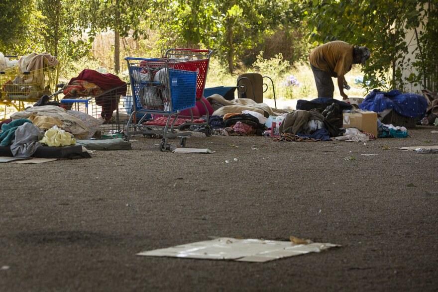 A man camps under an overpass under Ben White Boulevard.
