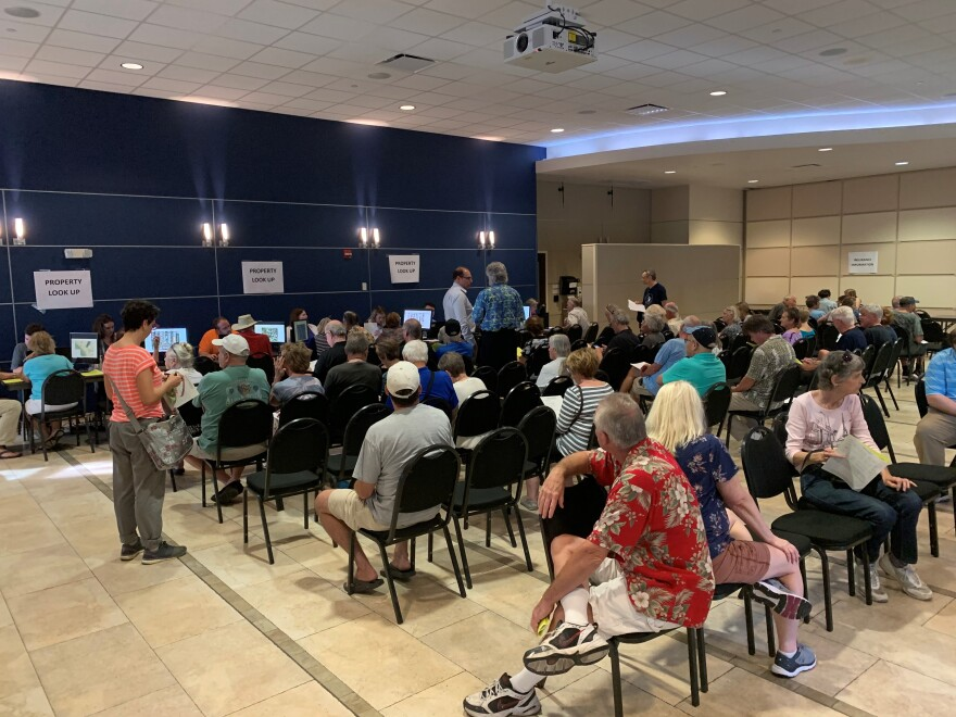 People sit in chairs and wait at a FEMA meeting