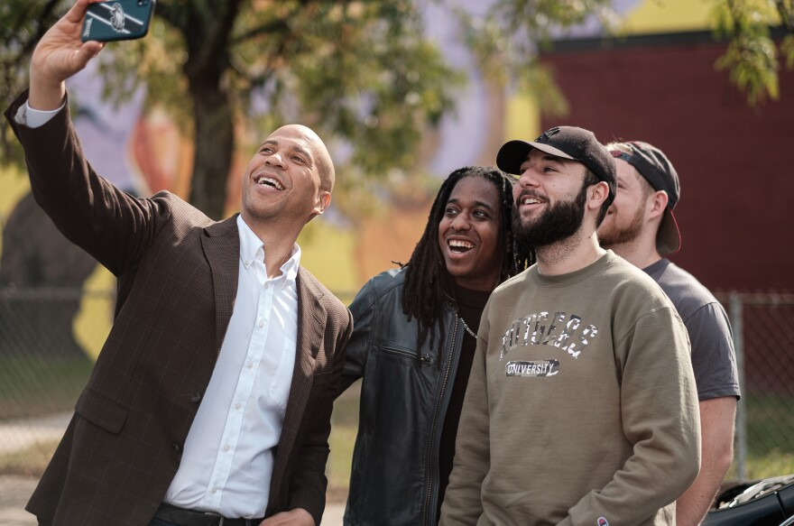 Presidential candidate Cory Booker takes selfies with supporters outside Vonda's Kitchen in Newark, N.J.