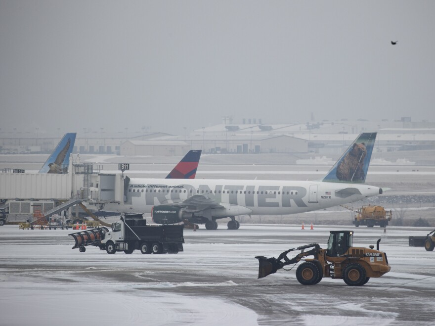 Snow removal vehicles clear ice from around airplanes at Nashville International Airport on Monday, in Nashville, Tenn.