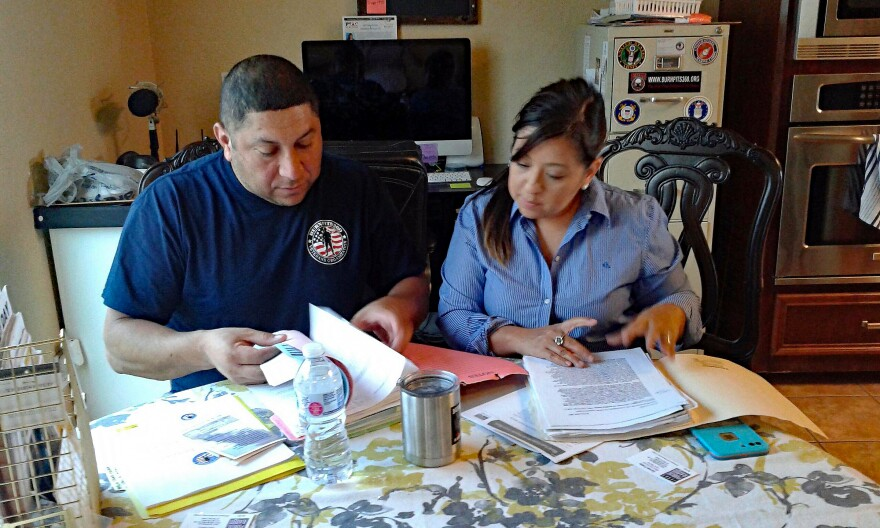 LeRoy and Rosie Torres review medical records at their home in Robstown, Texas.