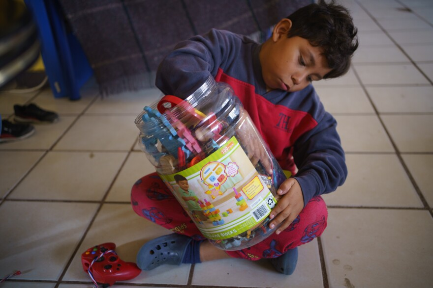 9-year-old Donovan sits on the tile floor looking through some secondhand toys in a large plastic jar.
