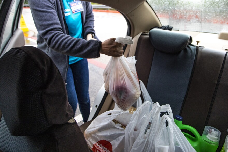 An H-E-B employee delivers groceries to a customer's car as part of the store's curbside pickup service.