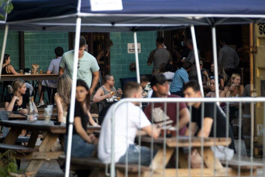 Patrons sit outside at a brewery last month after Texas eased restrictions.