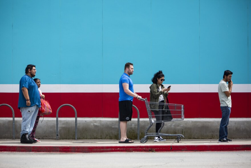 Shoppers stand apart from one another as they wait to enter an H-E-B grocery store in South Austin on March 23.