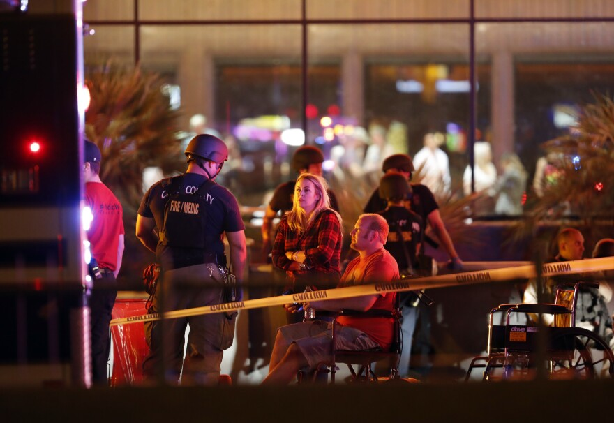 People wait in a medical staging area on Monday, after a mass shooting during a music festival Sunday on the Las Vegas Strip. Police say Stephen Paddock fired down at the crowd of more than 22,000 people from his room on the 32nd floor of the Mandalay Bay Resort and Casino.