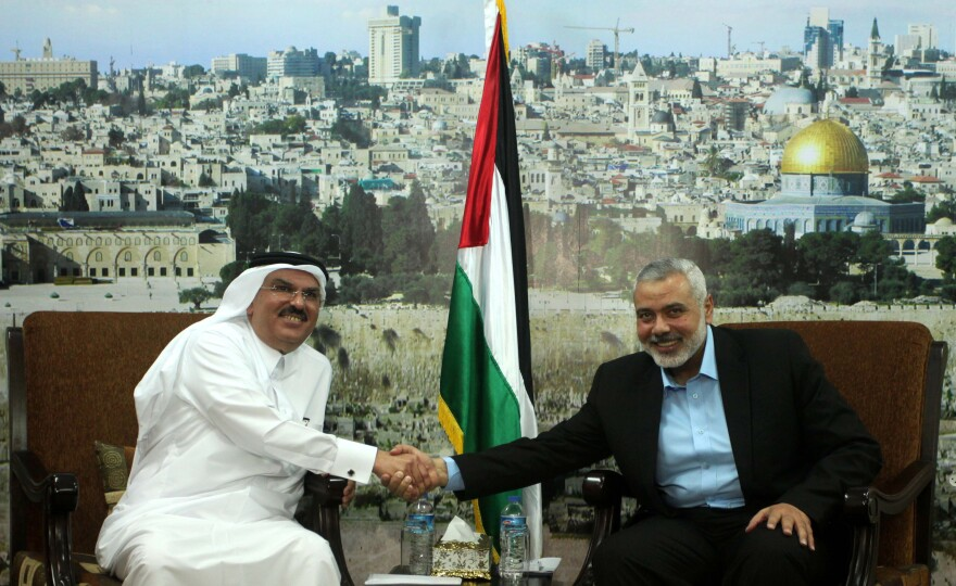 Qatari official Mohammed al-Emadi (left) visits Hamas leader Ismail Haniyeh in Gaza City on March 12. Israel has accused Qatar of financing Hamas weaponry but still allows Qatar to spends millions in Gaza on aid and development projects.