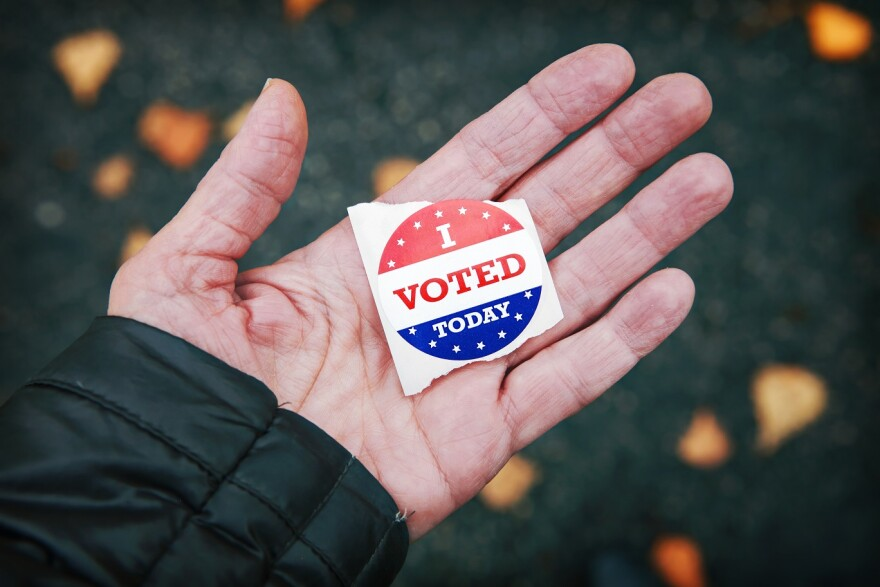 "a hand holding an ""I Voted Today"" sticker"