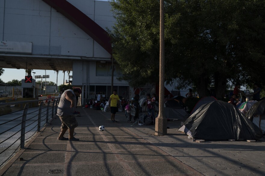 "Asylum-seekers pass their time in an encampment near the Gateway International Bridge in Matamoros, Tamaulipas in September. Most of them have been sent back under the ""Remain in Mexico"" program."