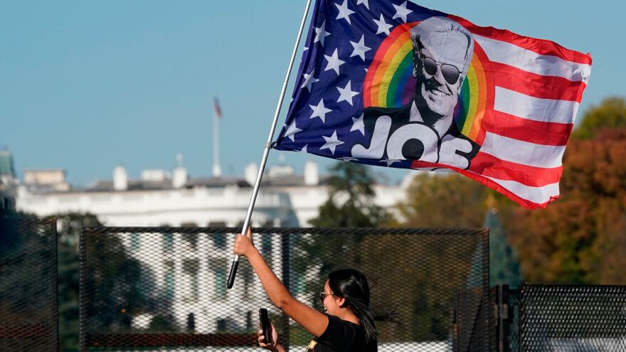 A woman waves a Joe Biden flag as people celebrate his presidential victory on Black Lives Matter Plaza across from the White House Saturday. Both Republicans and Democrats are offering their responses to the narrow defeat of President Trump.