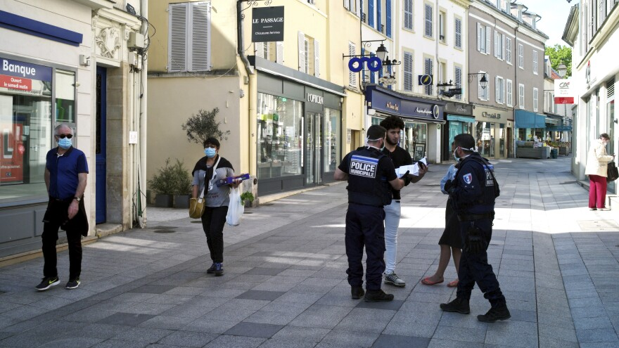 Police officers check documents as they enforce anti-coronavirus quarantine rules in Sceaux, France, on Wednesday. European Union leaders agreed on a package of measures Thursday to try to counter the economic damage from the lockdown.
