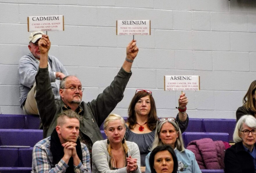 Residents held up signs naming the different heavy metals found in coal ash.