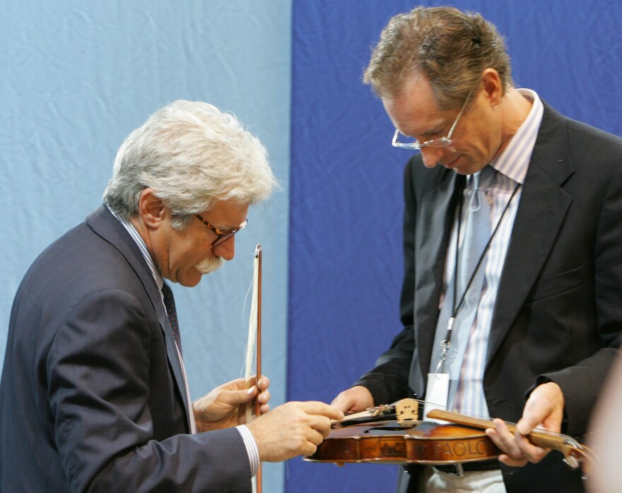 Appraisers Fred Oster (left) and David Bonsey, review a 1920 French violin at an <em>Antiques Roadshow</em> event in Los Angeles in 2005. Many stringed instruments throughout history have been made using small amounts of ivory.