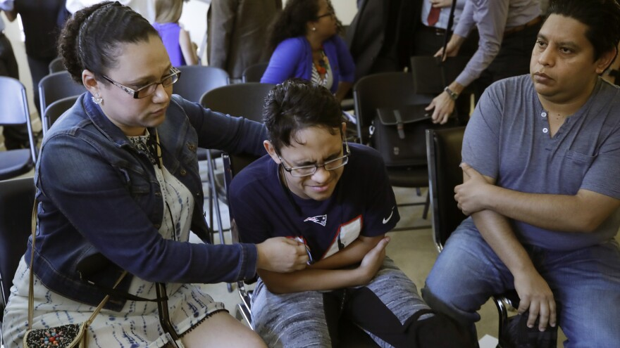 Gary Sanchez of Honduras (right) watches as his wife, Mariela, comforts their son, Jonathan, 16, during a news conference in Boston on Monday. The Sanchez family came to the U.S. seeking treatment for Jonathan's cystic fibrosis.
