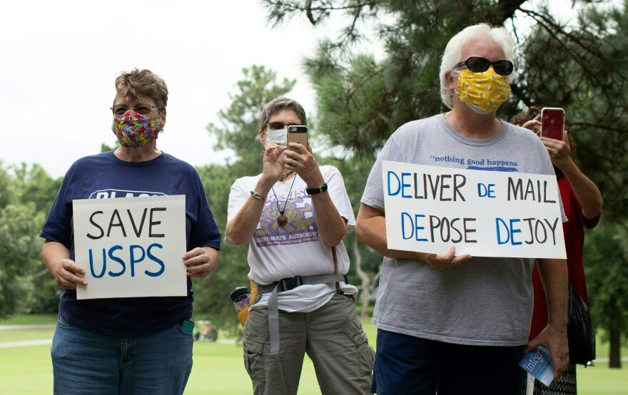 A group of protesters demonstrate in front of Postmaster General Louis DeJoy's home in Greensboro, N.C., on Sunday.