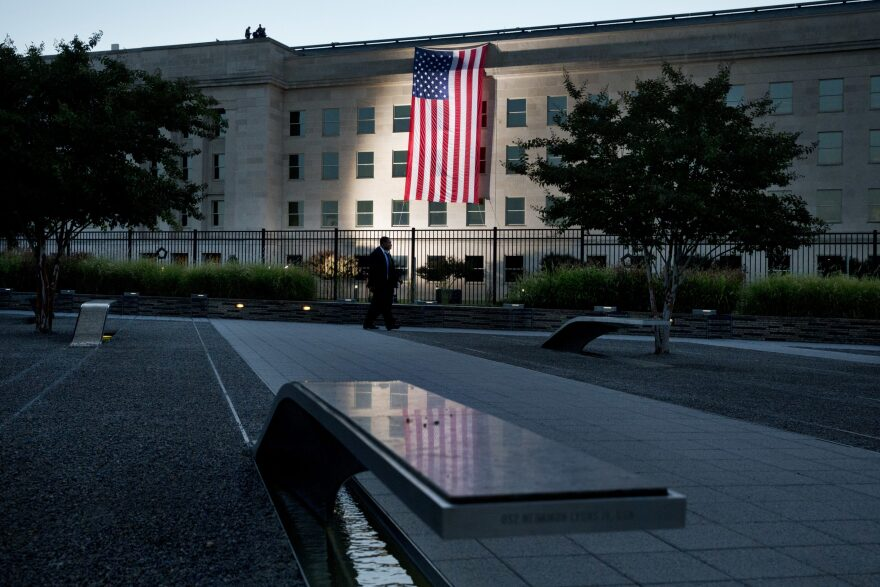 As seen from the Pentagon Memorial, a U.S. flag is draped on the side of the Pentagon where the building was attacked on Sept. 11 in 2001, on the 14th anniversary of the attack, Friday Sept. 11, 2015, in Washington. (Jacquelyn Martin/AP)