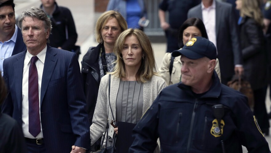 Felicity Huffman, center, departs federal court with her brother Moore Huffman Jr., left, Monday, May 13, 2019, in Boston, where she pleaded guilty to charges in a nationwide college admissions bribery scandal.