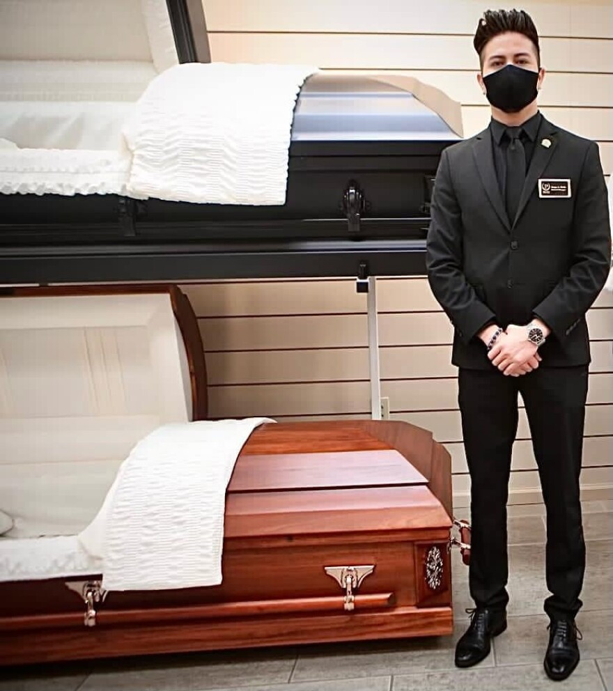 A man in black clothing and a black mask stands next to two coffins.