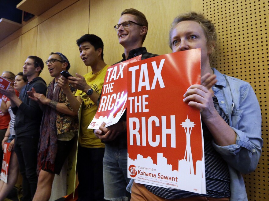 Audience members hold signs in support of a new city income tax on high earners at a Seattle City Council meeting on Monday.