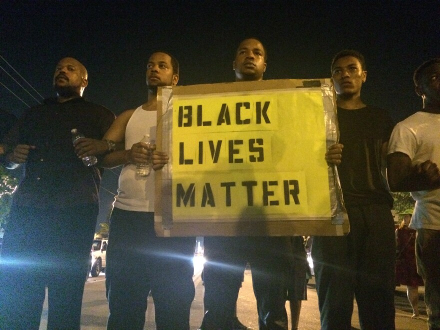 """At the closing of the protest, a line of people stood holding a sign saying """"black lives matter."""""""