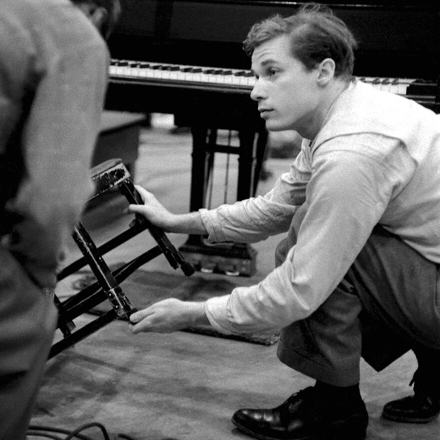Glenn Gould, in April, 1958, adjusts the special chair he uses to play the piano.