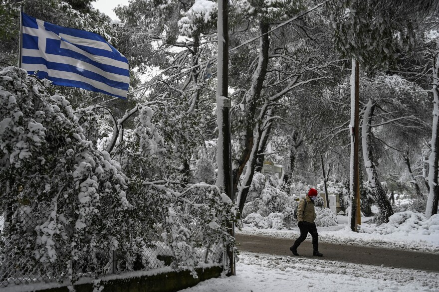 A man walks on a snow-covered street during snowfall in a northern suburb of Athens.