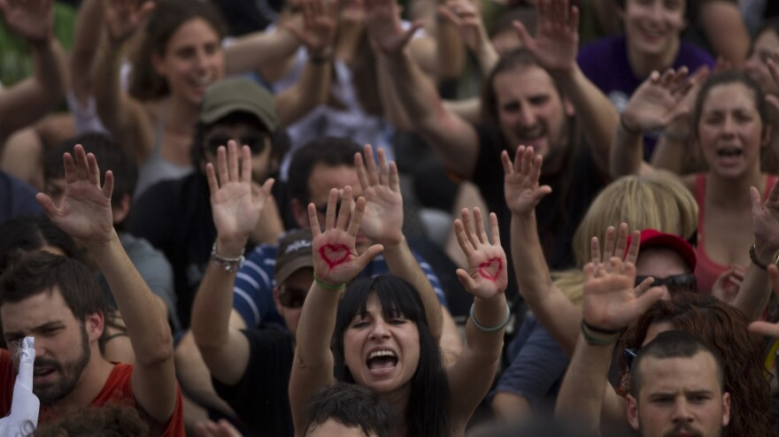"""Demonstrators shout slogans during a protest to mark the anniversary of the """"Indignados"""" movement in Madrid, Spain on Sunday. Tens of thousands of Spaniards took to the streets to protest the handling of the country's worst crisis in decades."""