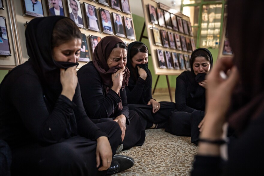 Women from Kocho weep as they remember family members killed in the genocide that began in August 2014, when ISIS declared Yazidis infidels.