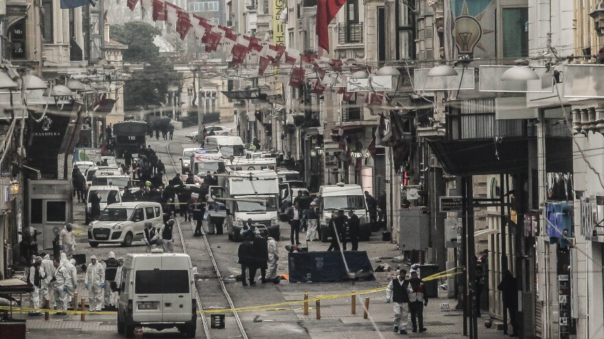 Emergency services inspect the area following a suicide bombing in a major shopping and tourist district in the central part of Istanbul on Saturday.