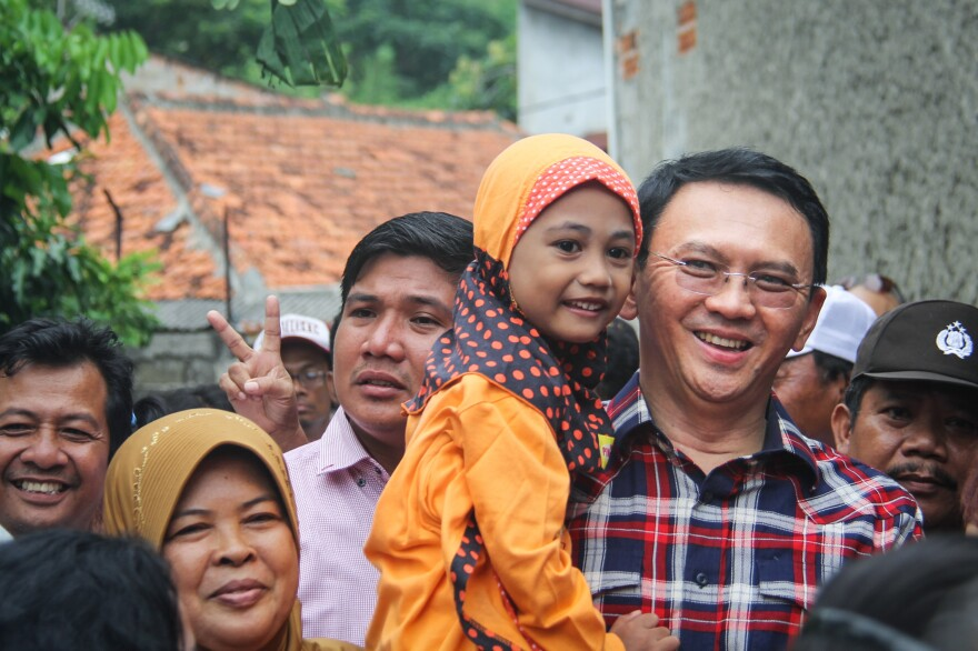 Residents and reporters follow Basuki Tjahaja Purnama, the first Christian, ethnic Chinese governor of Jakarta, as he campaigns for election in an East Jakarta neighborhood.