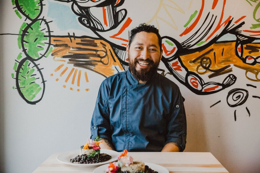 Chef Zaid Consuegra wearing a blue chef's jacket seated in front of a colorful mural with two plates of food on the table in front of him.
