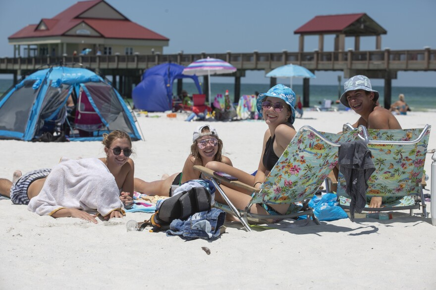 A group of teenagers sits on a beach towel at Clearwater Beach.