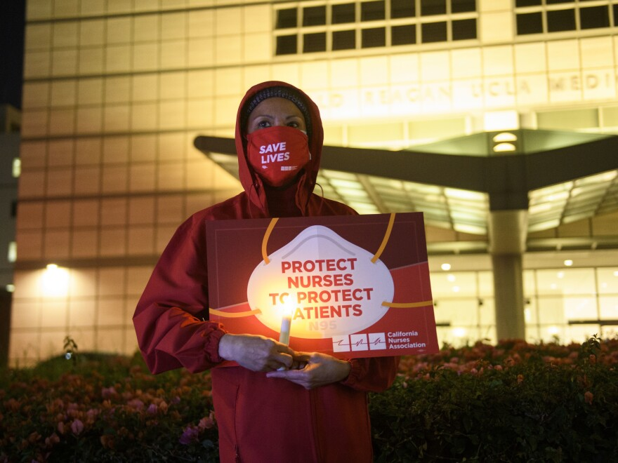 A nurse holds a candle during a vigil in Los Angeles last month for health care workers who have died from COVID-19. The vigil was organized by California Nurses United.