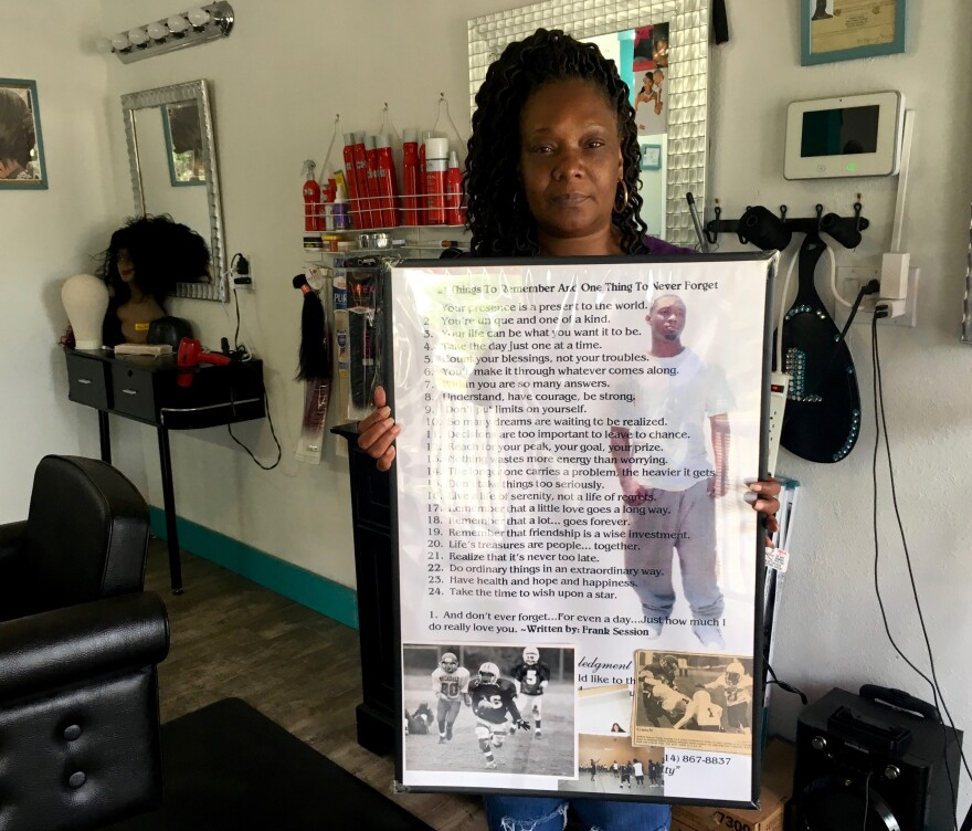 Tammy Riley holds a poem by her son, Frank at her daughter's beauty salon in the Greater Ville neighborhood. Frank died in a shooting outside a north St. Louis bar in 2009.