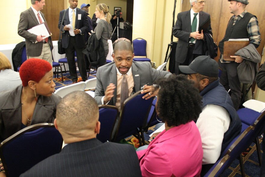 Starsky Wilson talks with attendees at Monday's Ferguson Commission meeting.
