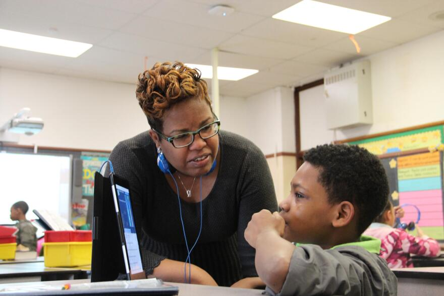 Ashland Elementary School Principal, Lisa Brown, helps students work through a classroom assignment using iPads.