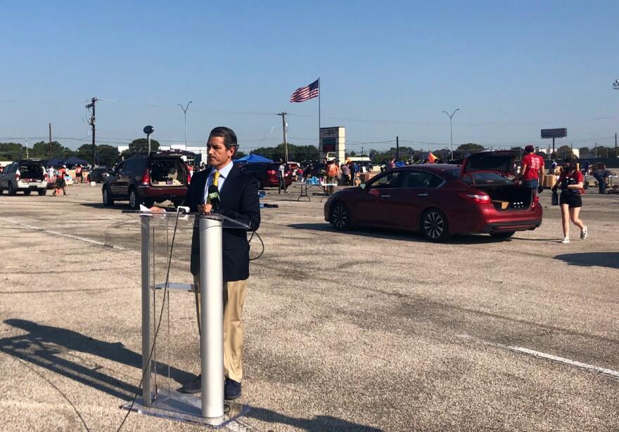 城市教育学院主任麦克·维拉里尔在志愿者将食物装载到他身后的汽车上时讲话。