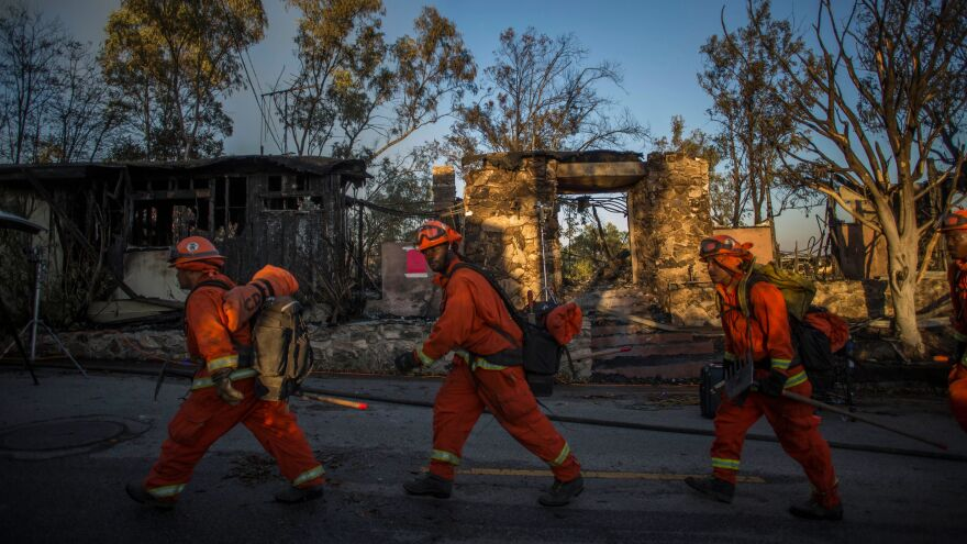 Inmate firefighters walk past a burnt building Monday in Brentwood, Calif., where the Getty Fire destroyed several homes and forced a partial shutdown of the busiest highway in the country.