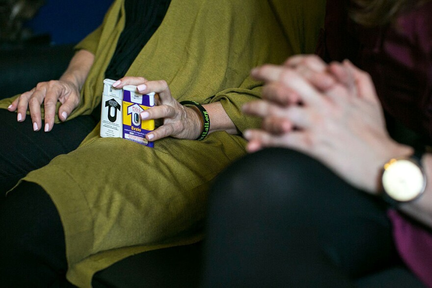 A woman lobbying Congress holds two versions of naloxone which can be used to reverse an opioid overdose.