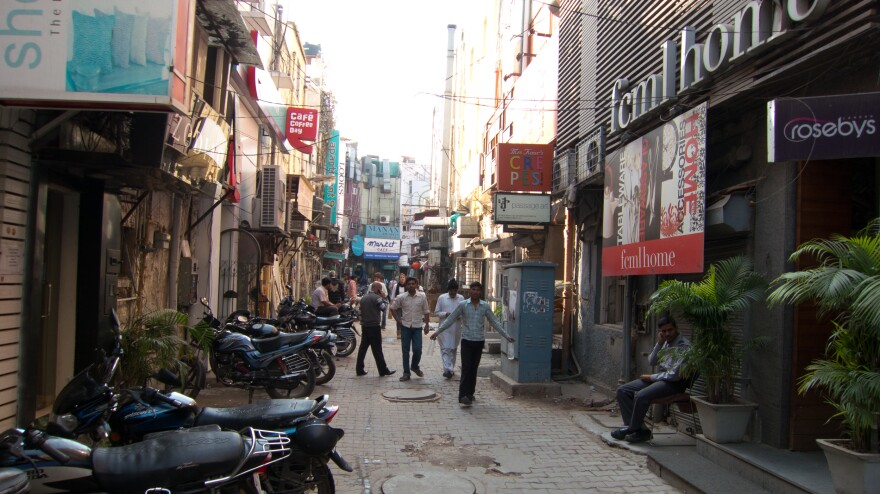 Khan Market is an upscale shopping district in Delhi. The wide streets are filled with luxury cars, and motorcycles line the narrower alleys.